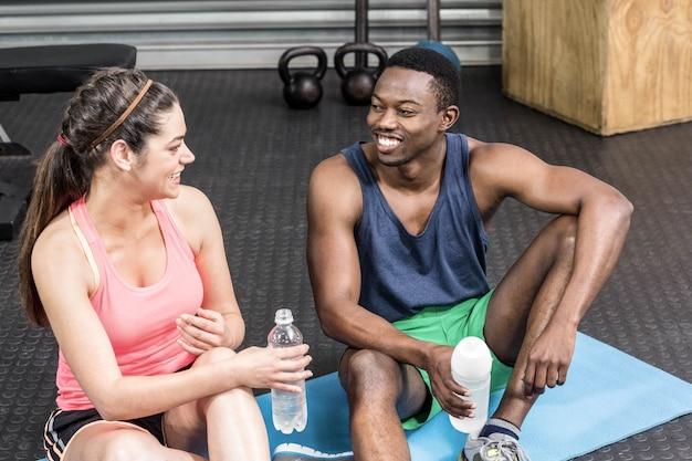 Donna ed uomo sorridenti che parlano sull'asciugamano di sport alla palestra del crossfit