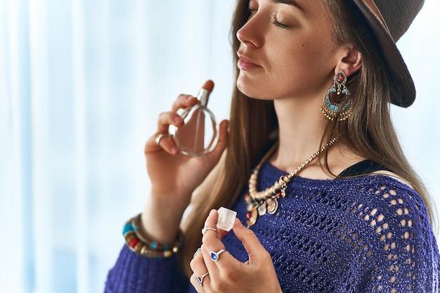 Donna elegante boho chic alla moda attraente bruna con gli occhi chiusi che indossa gioielli e cappello si applicano del profumo del profumo delle donne