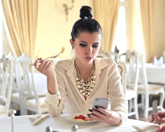 Donna elegante che controlla il suo telefono al tavolo