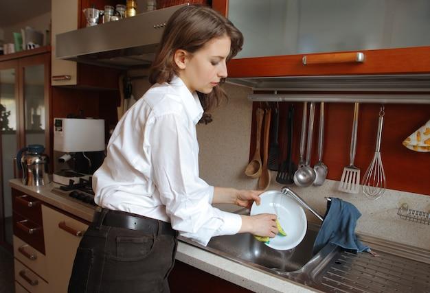 Donna elegante che fa i piatti in cucina