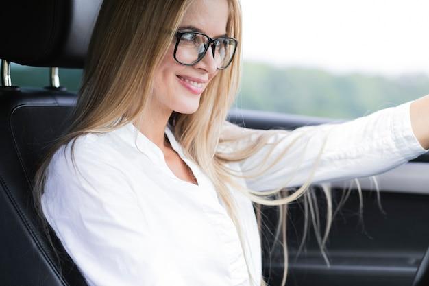 Donna elegante che guida la macchina