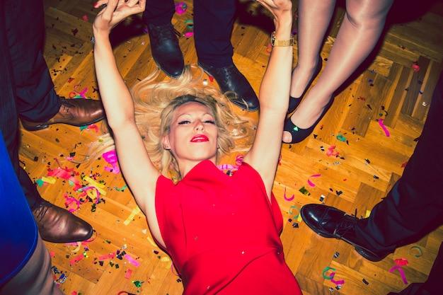 Donna elegante che pone sul pavimento al partito