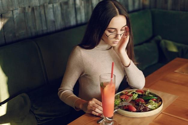 Donna elegante che si siede al tavolo con cocktail e insalata