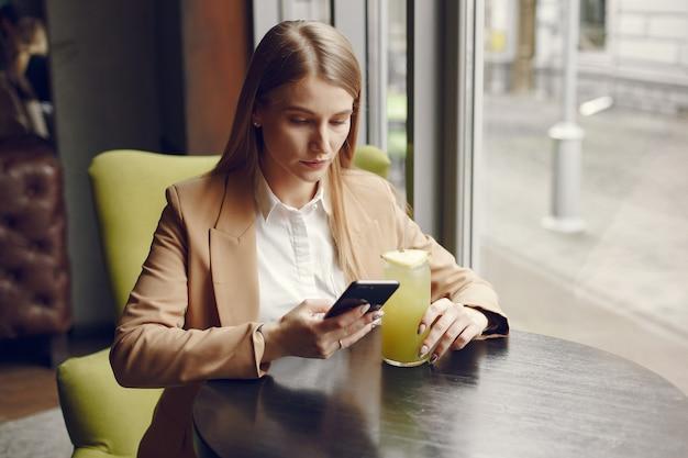 Donna elegante che si siede al tavolo con cocktail e telefono