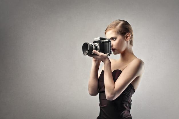 Donna elegante che tiene una macchina fotografica