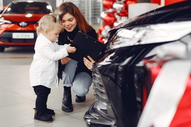 Donna elegante con la piccola figlia in un salone dell'automobile