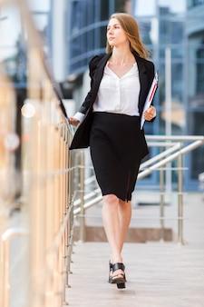 Donna elegante di affari che cammina alla macchina fotografica