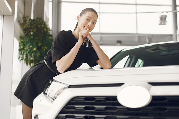 Donna elegante e alla moda in un salone di auto