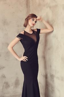 Donna elegante e glamour con abito nero in posa, concetto di moda