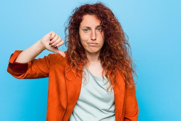 Donna elegante giovane rossa che mostra un gesto di antipatia, pollice verso il basso. concetto di disaccordo.
