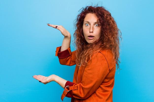 Donna elegante giovane rossa scioccata e stupita in possesso di uno spazio di copia tra le mani.