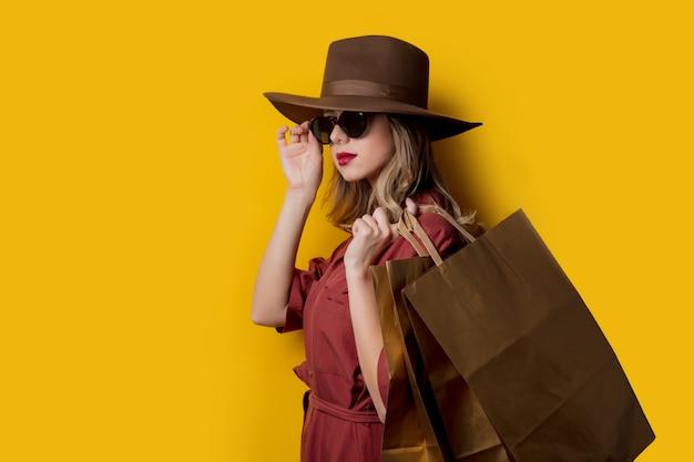 Donna elegante in occhiali da sole e con borse della spesa
