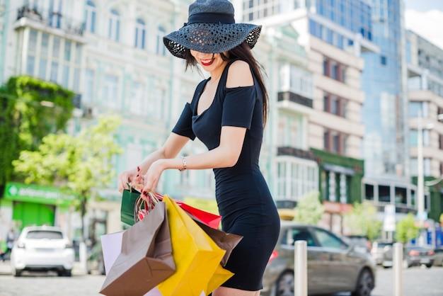 Donna elegante in sacchetti di vestito nero