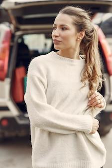 Donna elegante in un maglione bianco in una città di primavera