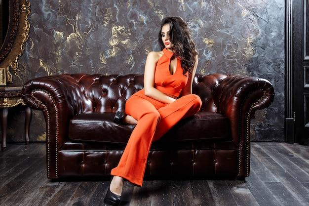 Donna elegante in un pantsuit rosso che si siede sul sofà