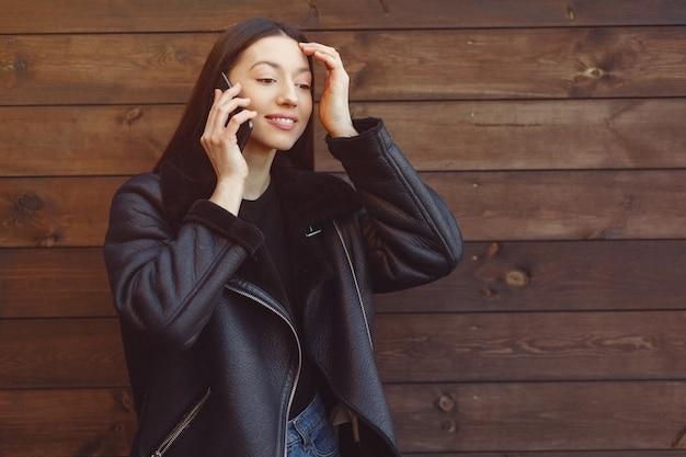 Donna elegante in una giacca nera in piedi su una parete marrone
