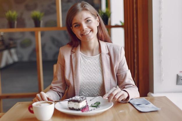 Donna elegante in una giacca rosa trascorrere del tempo in un caffè