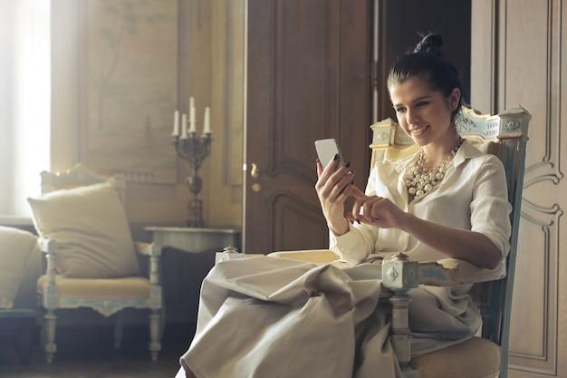 Donna elegante, navigare in rete su uno smartphone
