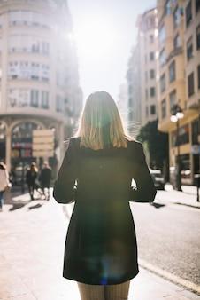 Donna elegante sulla strada in una giornata di sole