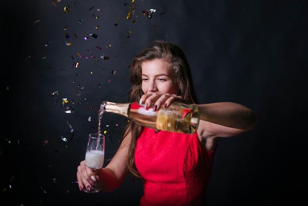 Donna emozionante che versa champagne