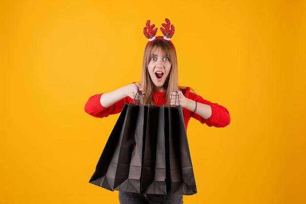 Donna emozionante con i regali in sacchetti della spesa di festa che indossano cerchio divertente