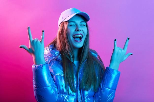 Donna emozionante felice che mostra gesto della roccia con le dita