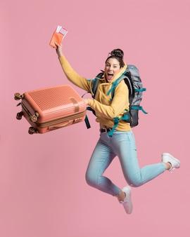Donna entusiasta che tiene il suo bagaglio e biglietto aereo