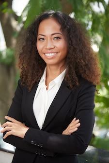 Donna esecutiva etnica felice che guarda l'obbiettivo