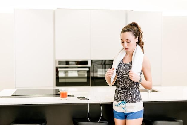 Donna esile di forma fisica che risolve a casa con la musica dal telefono