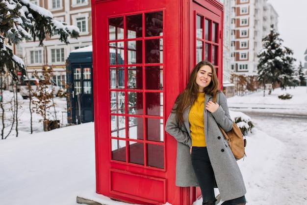 Donna estatica in maglione giallo alla moda in posa con piacere accanto alla cabina telefonica rossa in inverno. foto all'aperto di rilassata donna caucasica con zaino marrone divertendosi