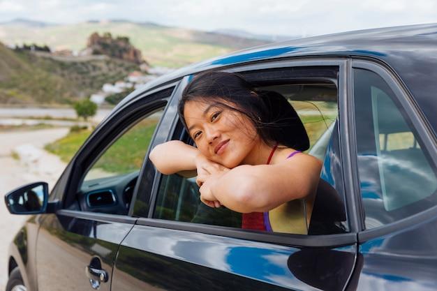 Donna etnica abbastanza giovane che si siede in macchina
