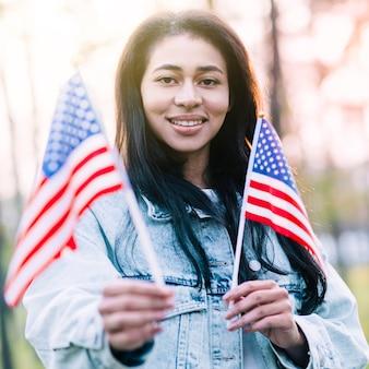 Donna etnica eccitata con bandiere americane souvenir