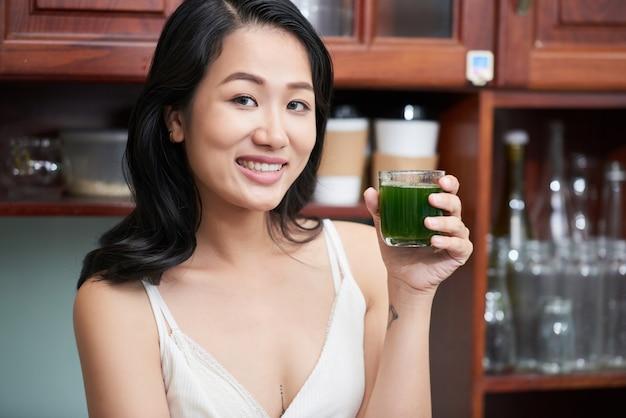 Donna etnica sorridente con bicchiere di succo