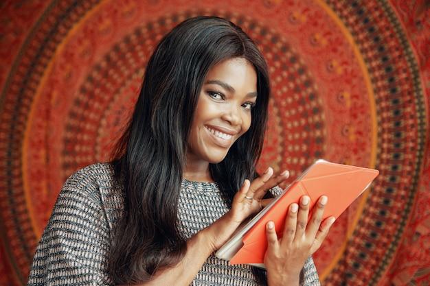 Donna etnica sorridente con tablet