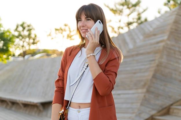 Donna europea che parla dal telefono cellulare mentre si cammina nel campus universitario o nel parco moderno.