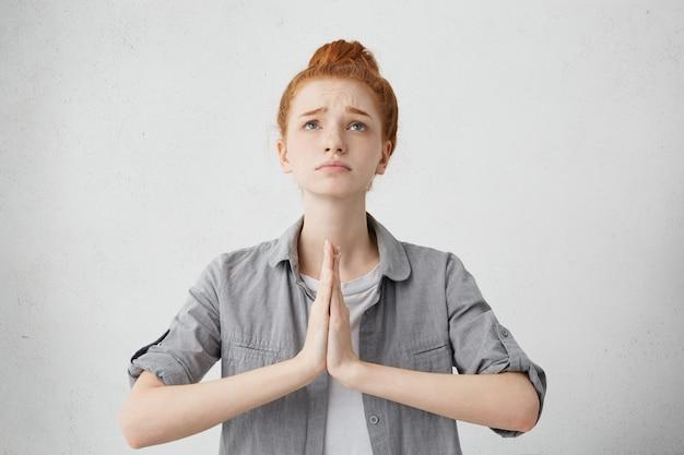 Donna europea rossa carina che tiene le mani davanti ai suoi palmi premendo insieme e guardando in alto, tenendo le sopracciglia sollevate, pregando
