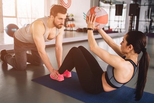 Donna facendo qualche esercizio addominale con la palla mentre il suo compagno di sport sta tenendo le gambe sul pavimento. l'aiuta a fare esercizio fisico nel modo giusto.