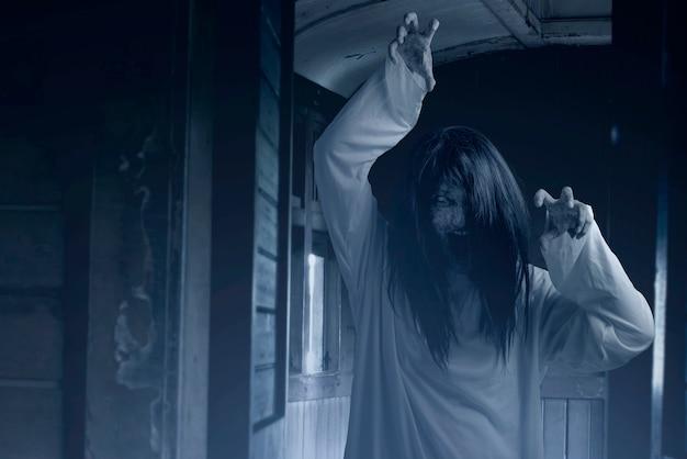 Donna fantasma spaventosa con sangue e faccia arrabbiata con le mani da artiglio sul vecchio vagone