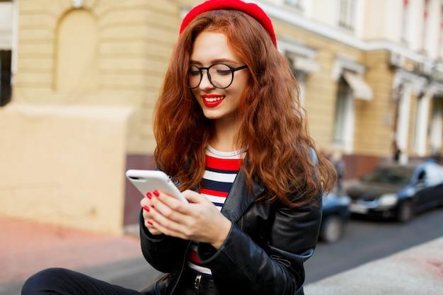 Donna favolosa felice dello zenzero in berretto rosso alla moda nella via facendo uso dello smartphone