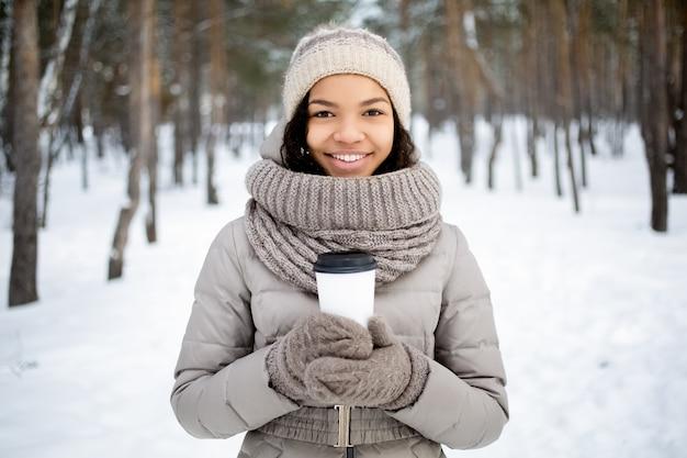 Donna felice africana con tazza di caffè in inverno