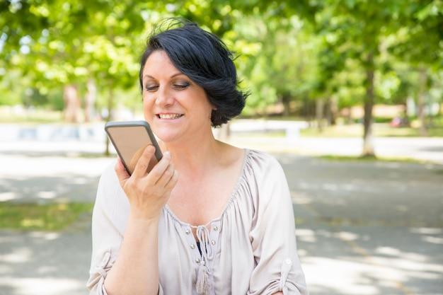 Donna felice allegra che parla sull'altoparlante