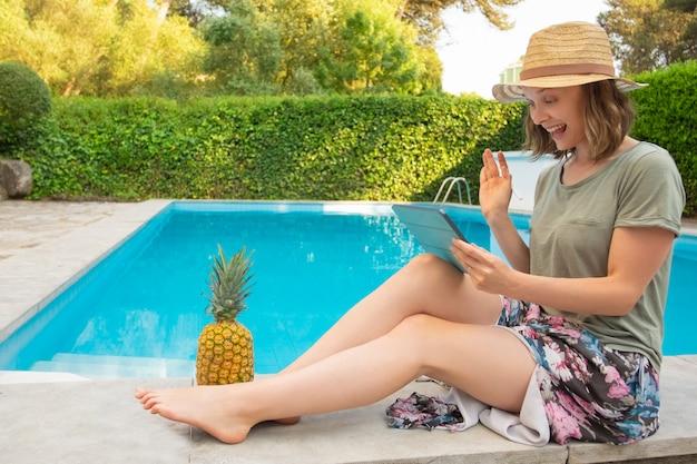 Donna felice allegra con la compressa che si siede alla piscina