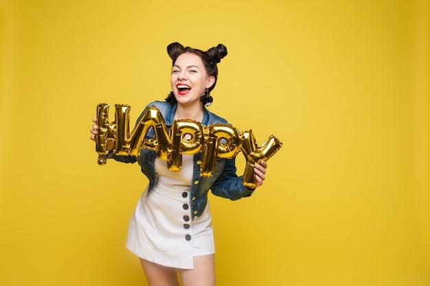 Donna felice attraente che ride tenendo le grandi lettere dell'oro che posano al fondo giallo dello studio