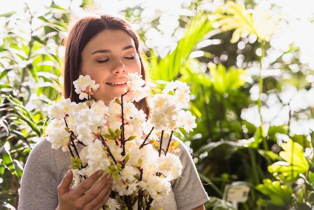 Donna felice attraente che tiene mazzo di ramoscelli di fiori