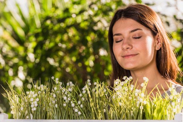 Donna felice attraente vicino a piante fresche
