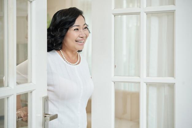 Donna felice che accoglie favorevolmente gli ospiti