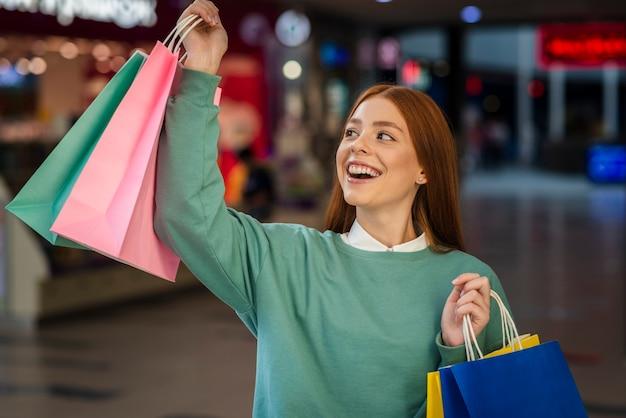 Donna felice che alza i sacchetti della spesa