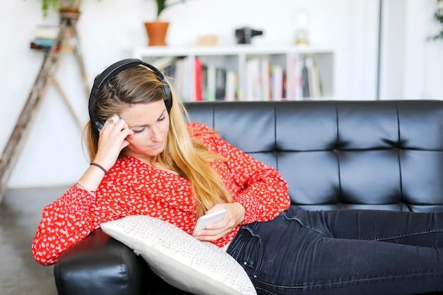 Donna felice che ascolta la musica che indossa le cuffie facendo uso di uno smartphone che si siede su un sofà