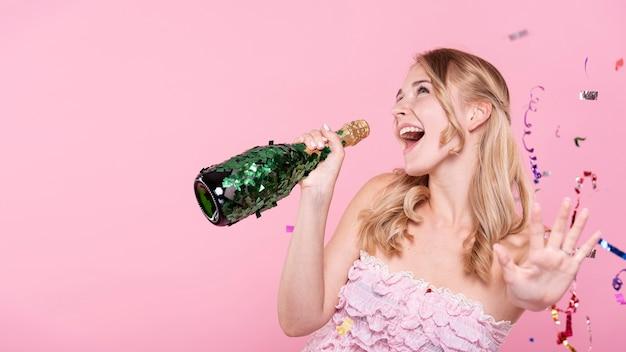 Donna felice che canta alla bottiglia di champagne