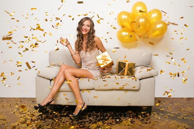 Donna felice che celebra il nuovo anno in coriandoli dorati che si siede sul divano